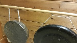 Photo 1 - Closeup view of screw hooks on a wooden rail supporting gongs