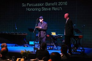 Steve Reich accepting the pulse 'piece of wood' from Jason Treuting at Sō Percussion Benefit Concert, May 17, 2016. Photo: Marc Akiyama.